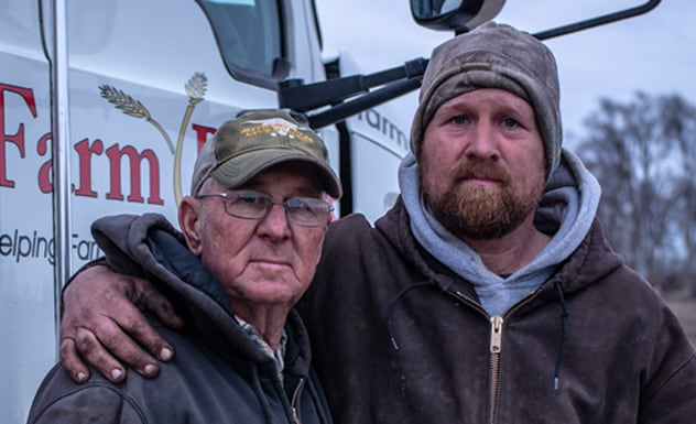 One man with his arm around the other in front of a Farm Rescue truck