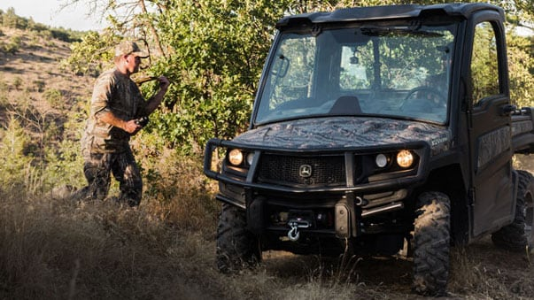 Man and camo gator in rough terrain