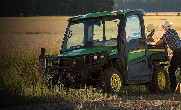 Two ranchers loading bales of hay in the back of a Gator™ XUV835R.