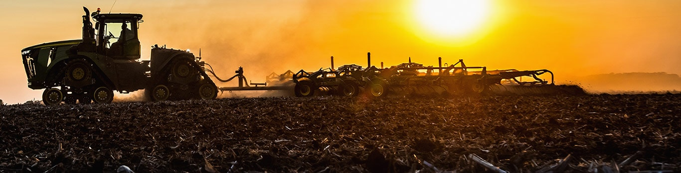 Tractor tilling spring field at sunset