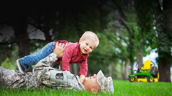 Uniformed man holding child on ground in front of mower.