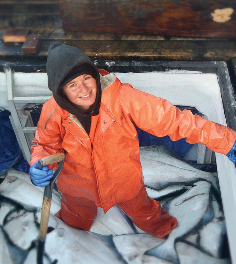 Female Captain Michelle Rittenhouse stands smiling in her boat's cargo hold full of large fish.
