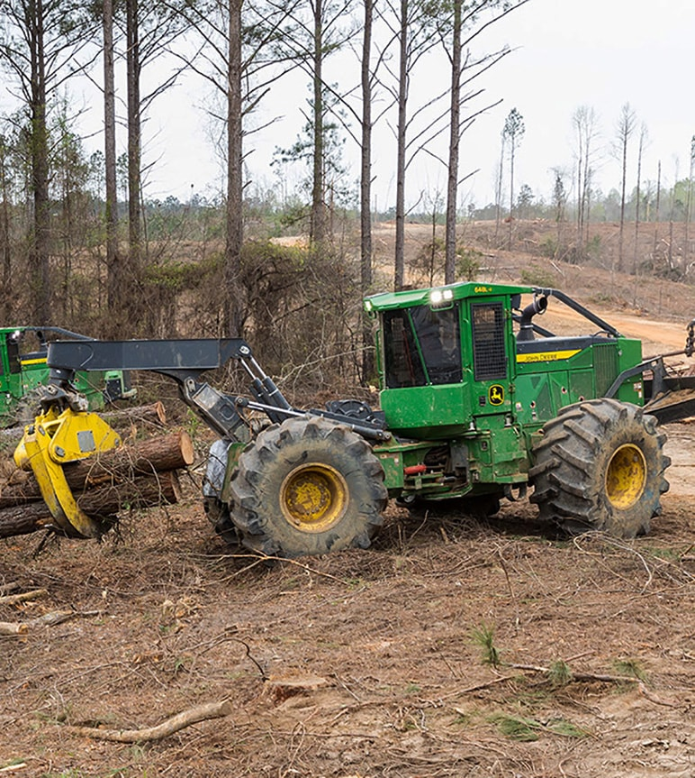 Skidder carries a bundle of logs in a forestry work site.