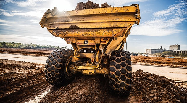 Back end view of a 410E-II dump truck in mud