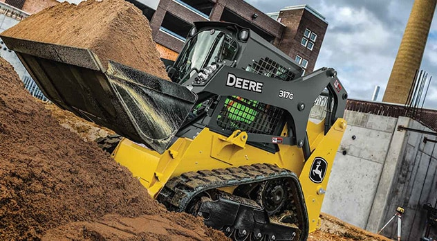 317G Compact Track Loader pushing dirt on a jobsite
