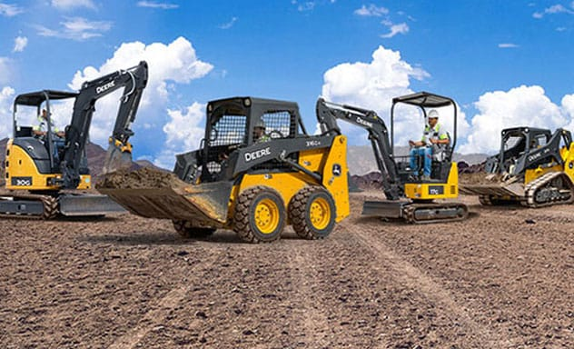 Skid steers, mini excavators and a compact track loader line up on a jobsite with a blue sky background