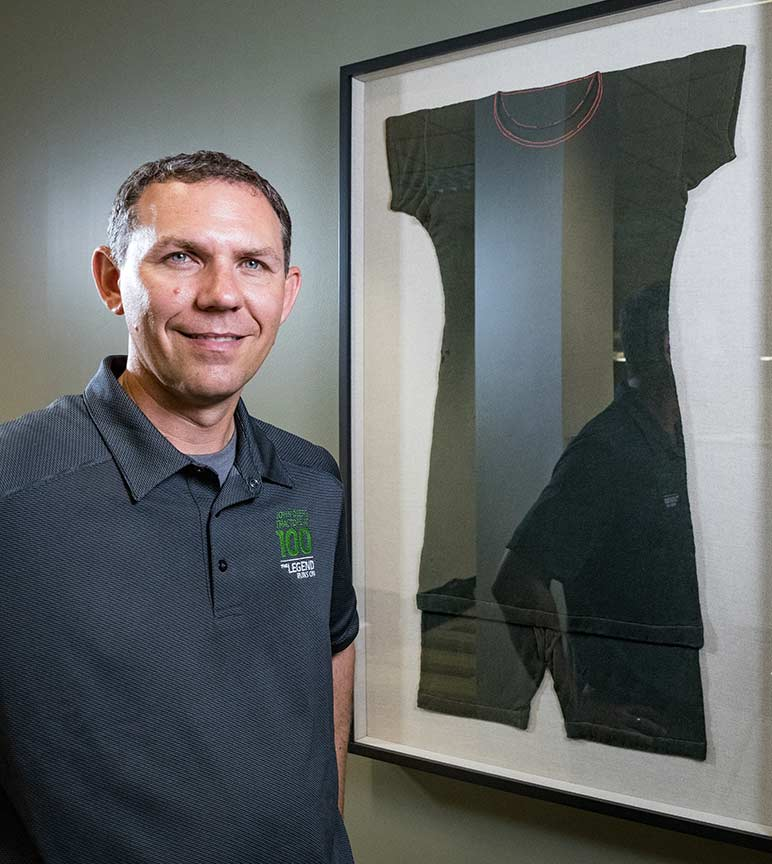 Neil Dahlstrom stands by John Deere's framed swimsuit.