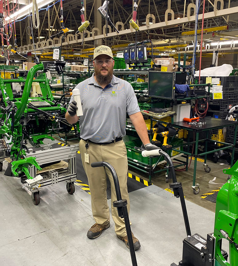 Jason Sherron, assembly manufacturing engineer, holds PUSH protective handles made from PVC pipe to fit over assembly cart handles.