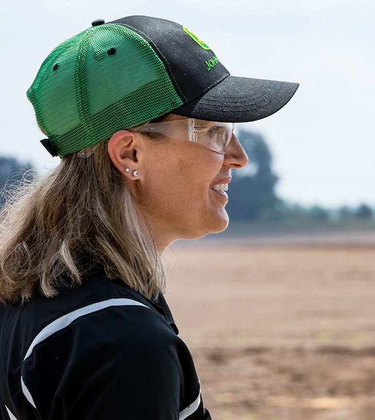 Profile of smiling woman in field wearing protective eyewear and John Deere hat.