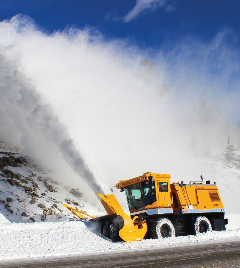 A loader-mounted snow-blower blowing snow off of a highway.