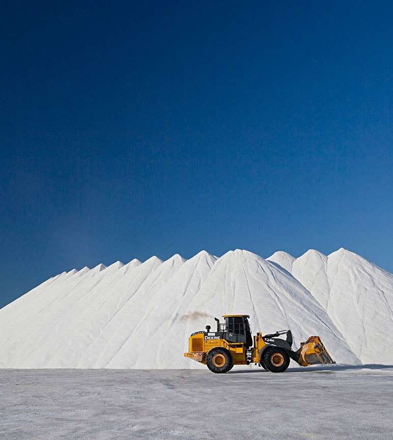Wheel Loader in front of large piles of salt.