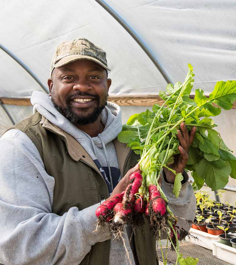 Jon Jackson showing radishes he has harvested.