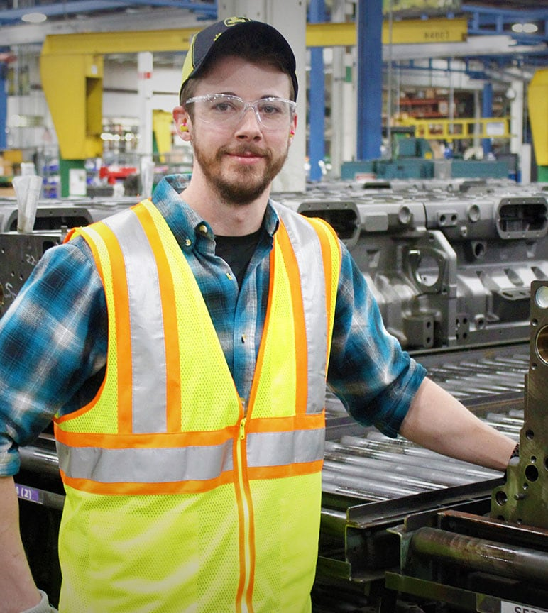 Employee Josh Ming stands smiling and wearing safety gear in front of a parts remanufacturing line.