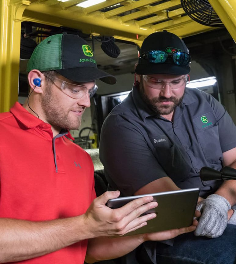 One John Deere factory employee shows his tablet to another employee sitting in a forklift.
