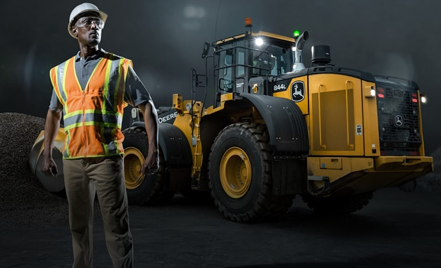 Man in construction gear stands in front of 844L Wheel loader scooping gravel