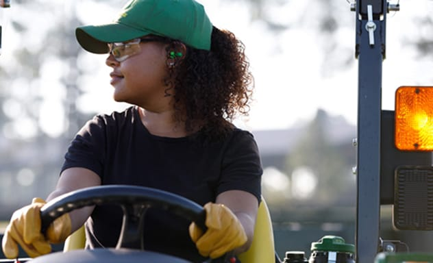 Closeup image of a woman driving a Compact Utility Tractor.