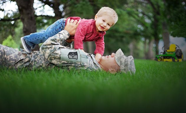 Man in military fatigues laying on grass holds smiling child above him, John Deere mower in background.