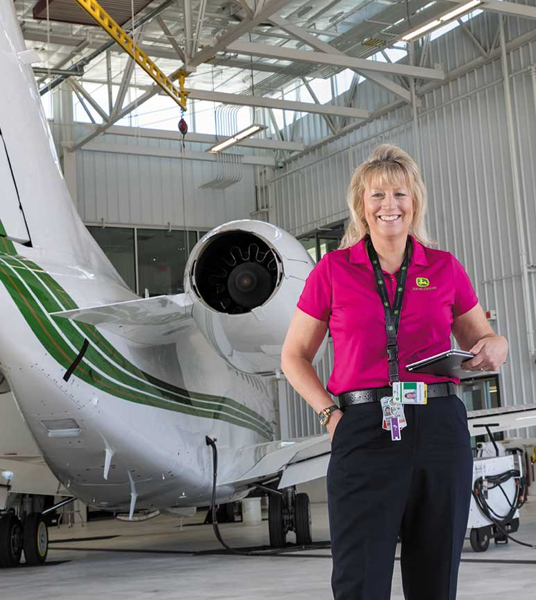 Woman stands in front of airplane in hanger.