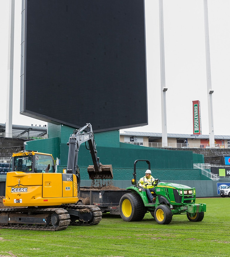 Excavator and tractor on baseball field in front of scoreboard.