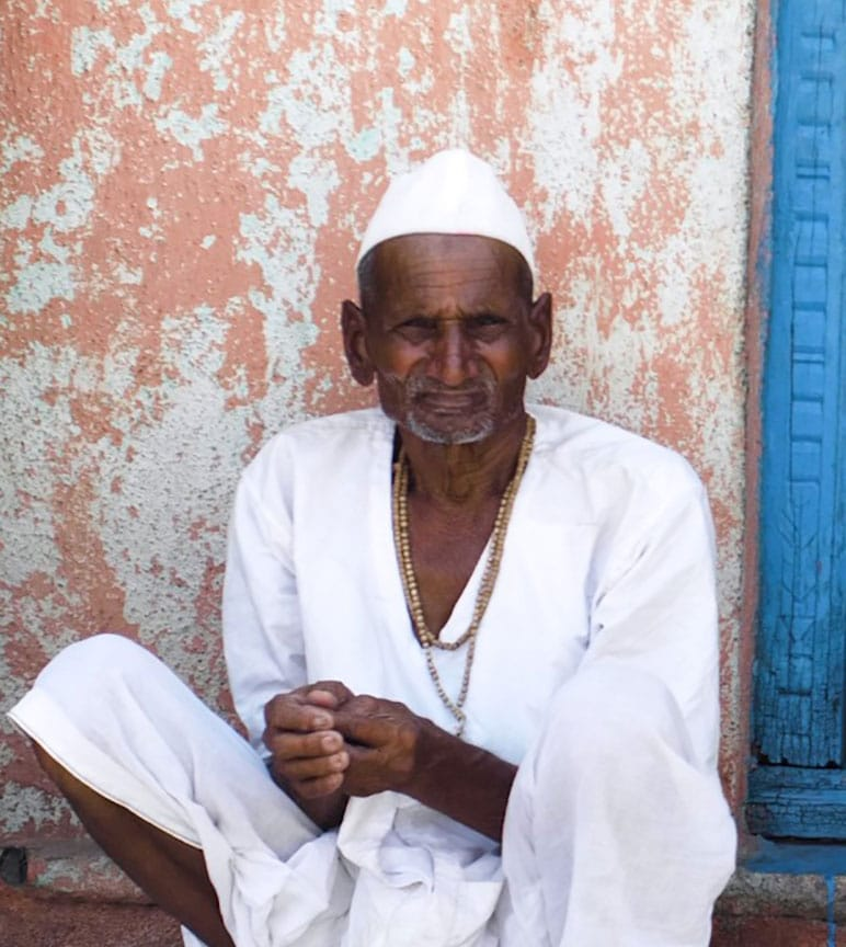 Indian man sits leaning against wall.