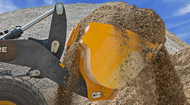 Close up of a loader bucket scooping up fine gravel from a large pile