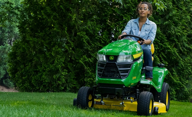 Woman wearing safety glasses operates a riding lawn mower on grass