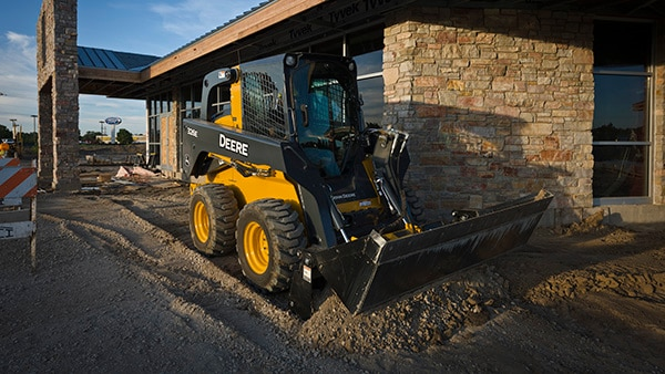 326E Skid Steer with multi-purpose bucket attachment at a commercial building jobsite.