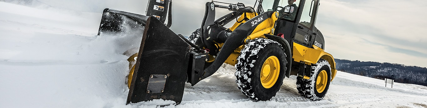 324K Compact Loader with Snow Blower attachment blowing snow off a road