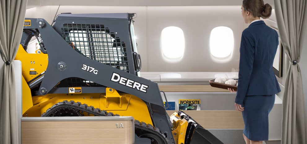 317G Compact Track Loader in first class on an airplane with a flight attendant offering refreshments