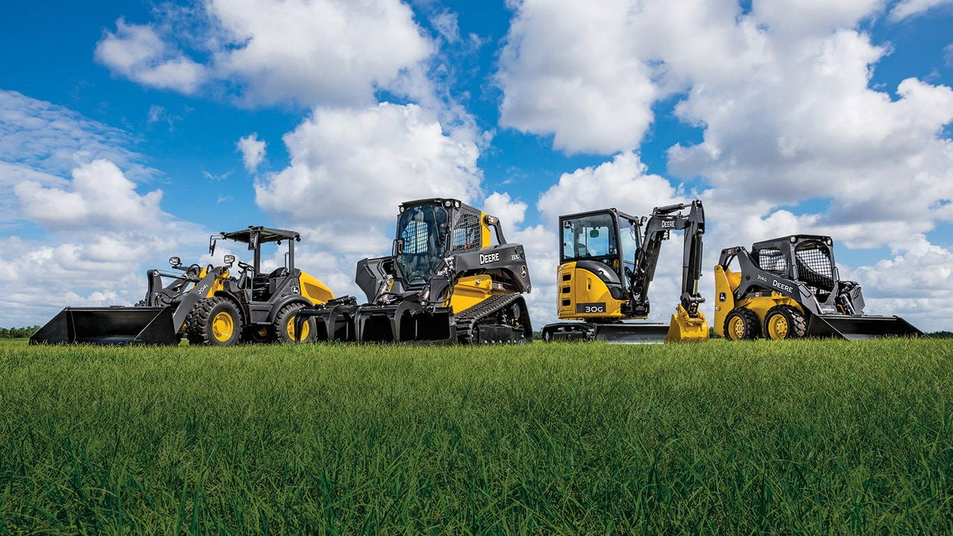 compact track loader, compact wheel loader, compact excavator and skid steer sit in a grassy field with blue sky and white clouds