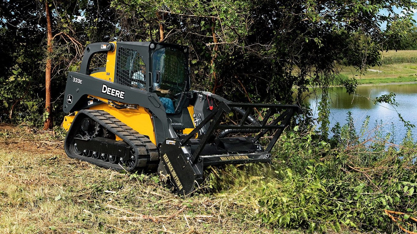 Mulching head on a compact track loader chopping material near a pond.