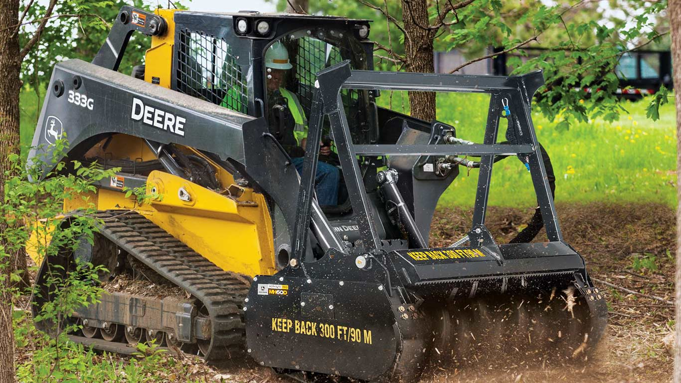 A John Deere 333G Compact Track Loader with a MH60D Mulching Head attachment at work on a residential site.