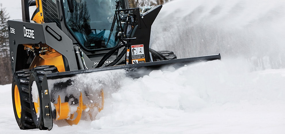 326E Skid Steer with Snow Blower attachment blowing snow off a road
