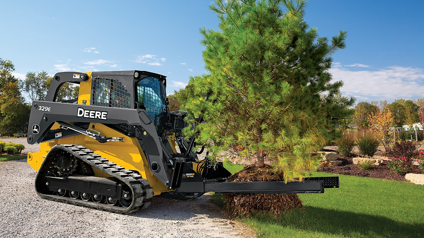 329E Compact Track Loader with nursery fork attachment relocating a pine tree.