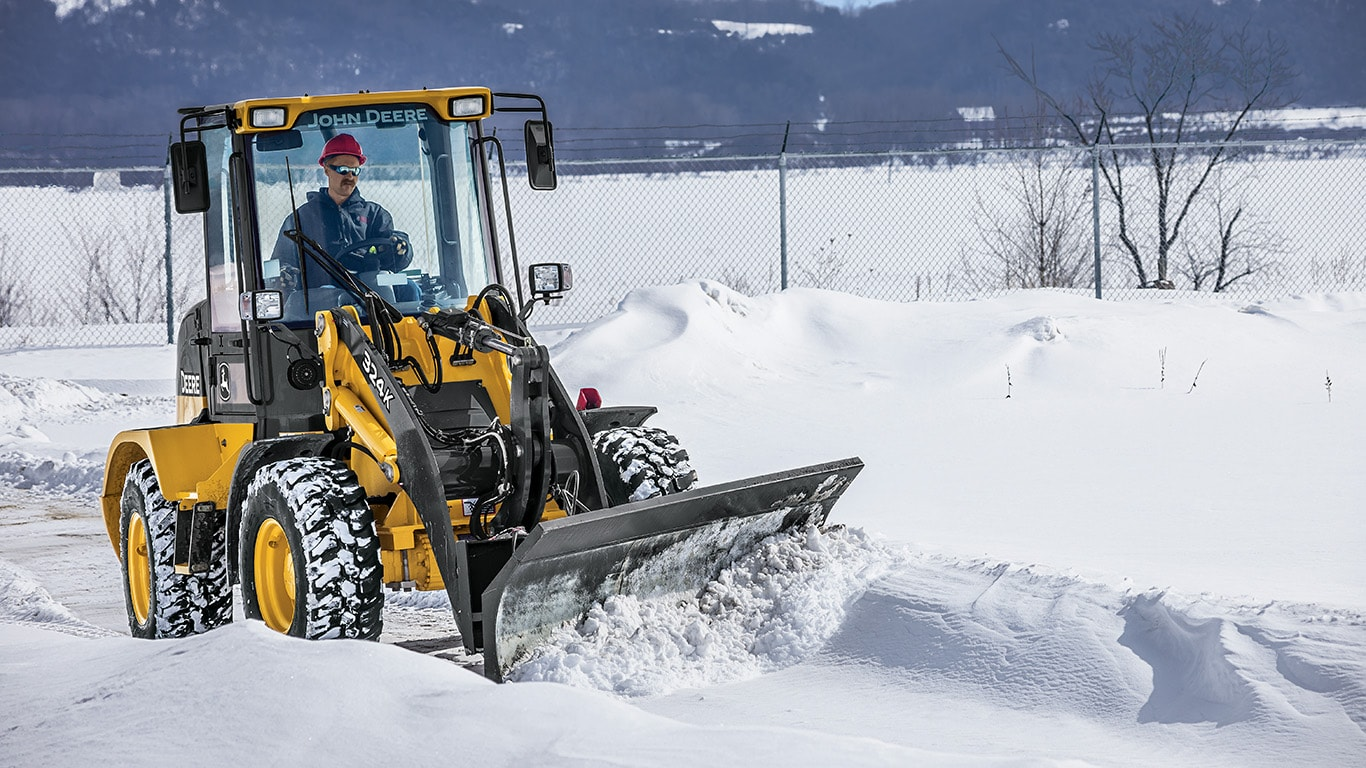 324K Compact Loader with snow blade pushing snow off a road.