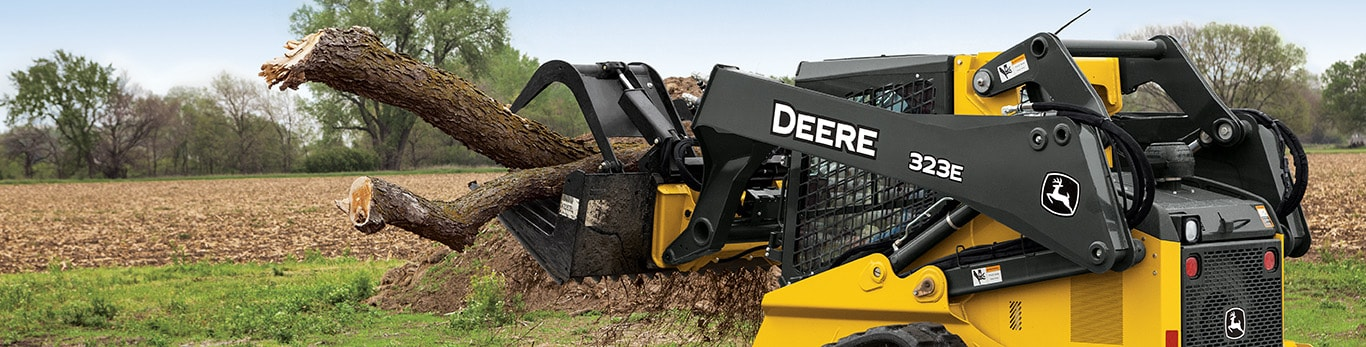 323E Compact Track Loader with Grapple attachment moving large tree branches