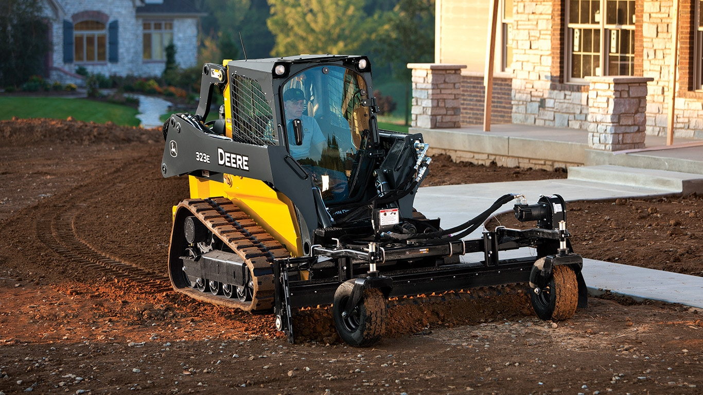 Compact Track Loader with power rake attachment, working at a residential jobsite.