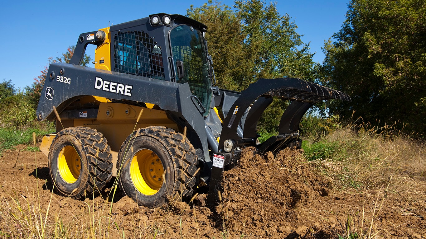 332G Skid Steer with Root Rake attachment working on a jobsite.