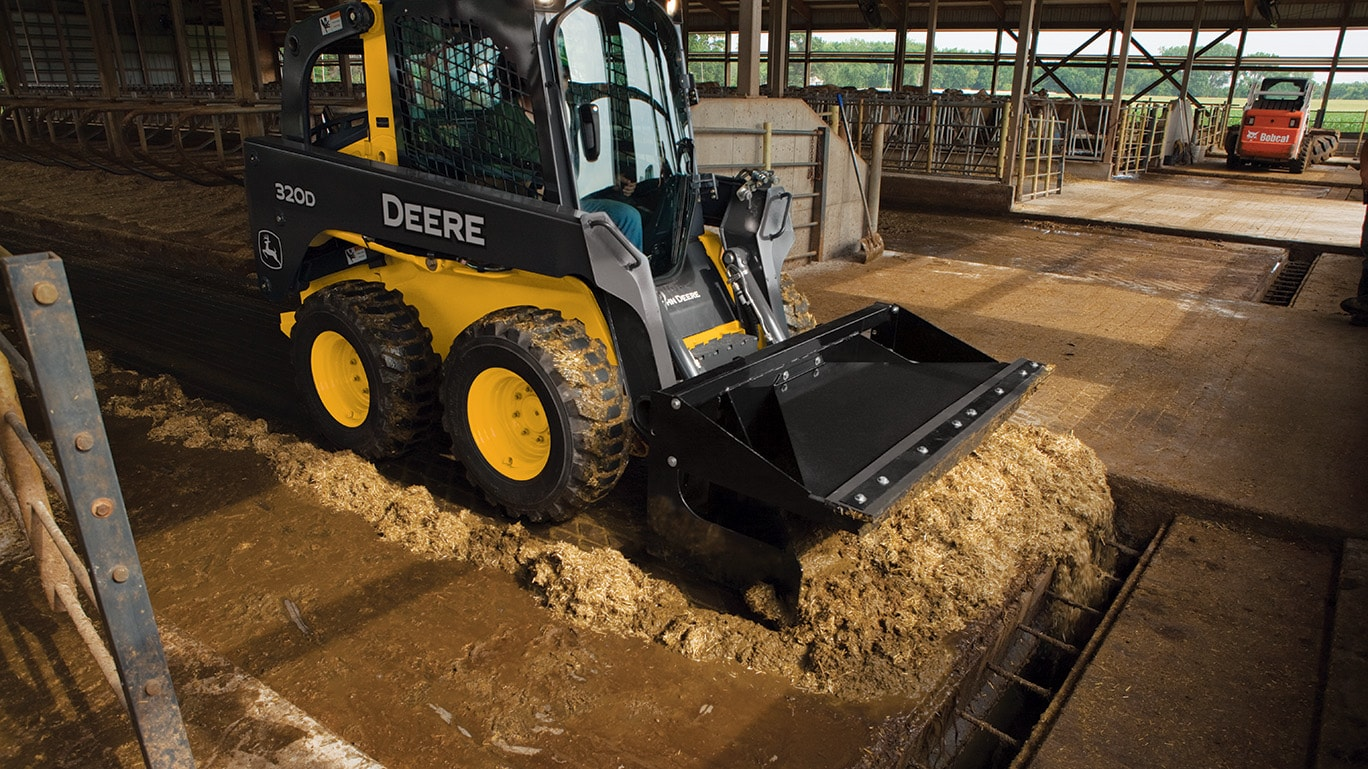 320D Skid Steer with material scraper working in a livestock confinement