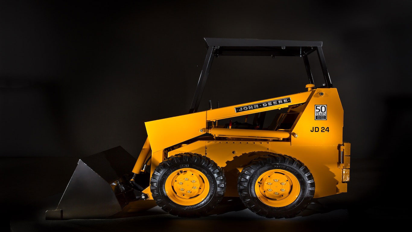 A 1970 JD24 Skid Steer Loader on a black background.