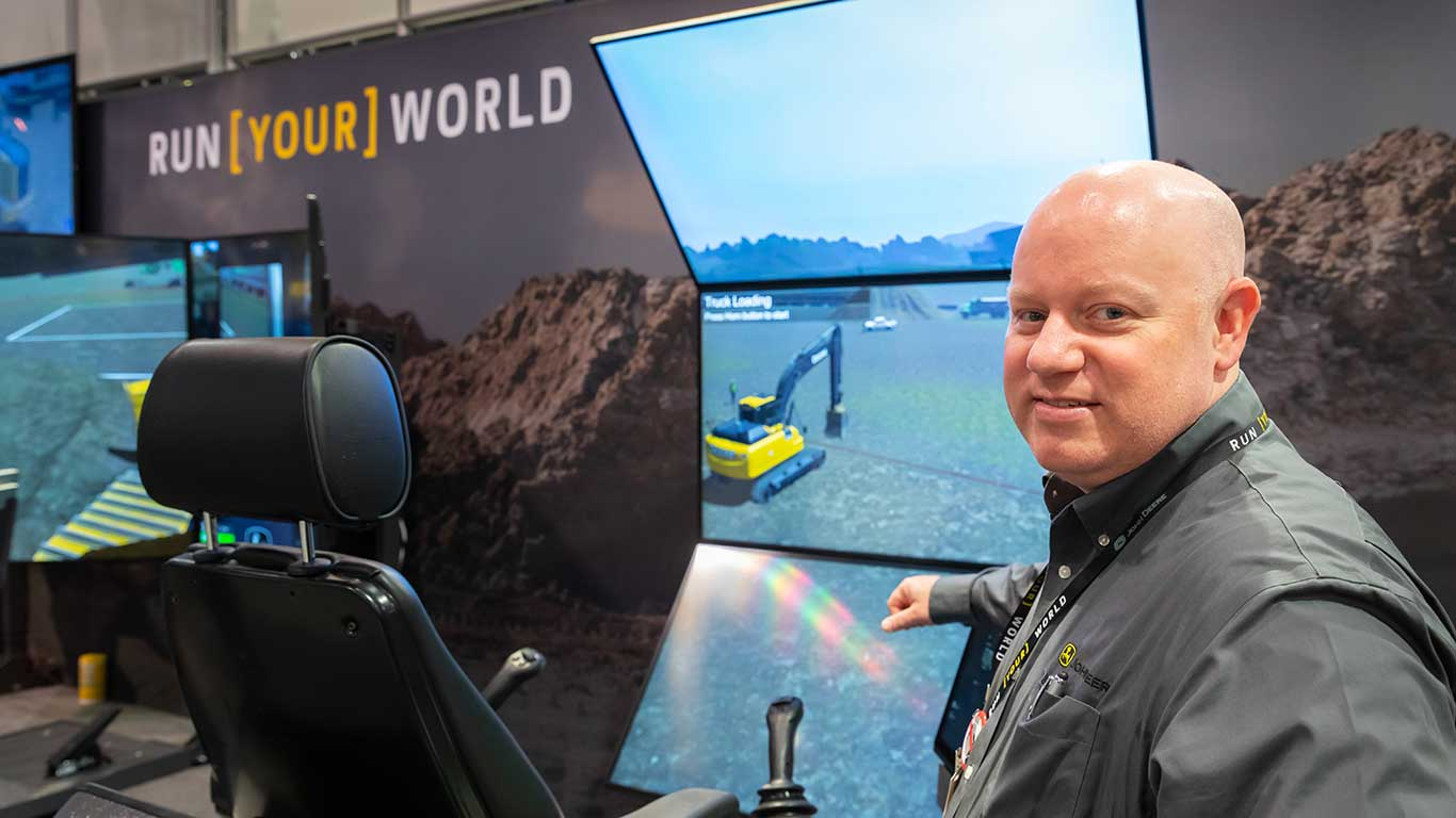 A Deere employee stands by a simulator