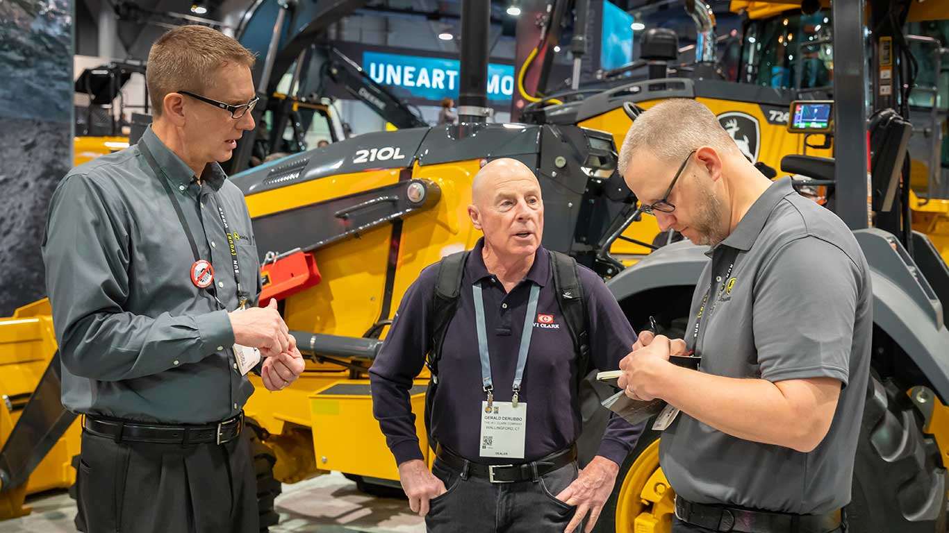 Two Deere employees speak to an attendee in front of a 210L Loader