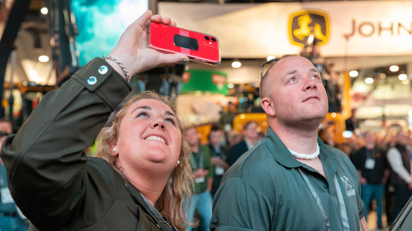 Two attendees smile and take a picture with their phones inside the Deere booth