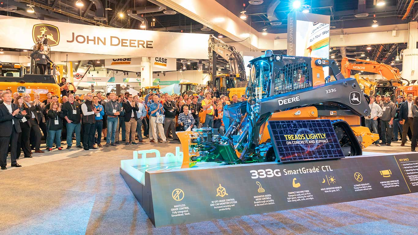 A crowd gathers around the 333G SmartGrade Compact Track Loader with integrated grade control