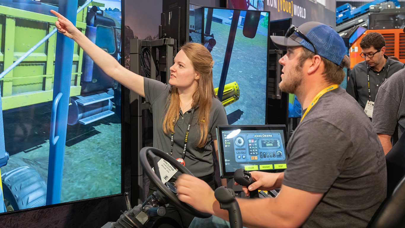 A man tries out an equipment simulator with a Deere employee helping him