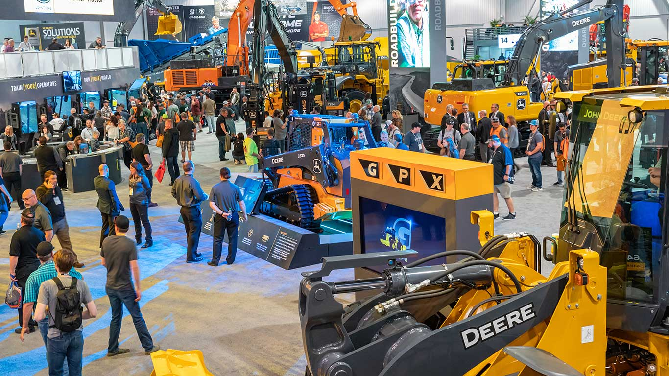High-level view of the booth showing John Deere's performance tiering display and many earthmoving machines