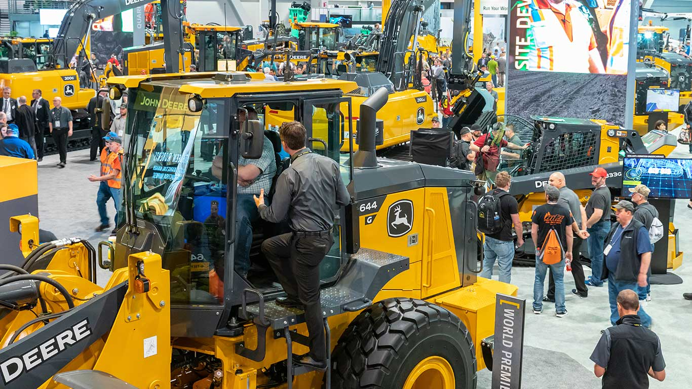 A Deere employee stands on the ladder of the 644 G-Tier Loader talking to a customer in the cab.