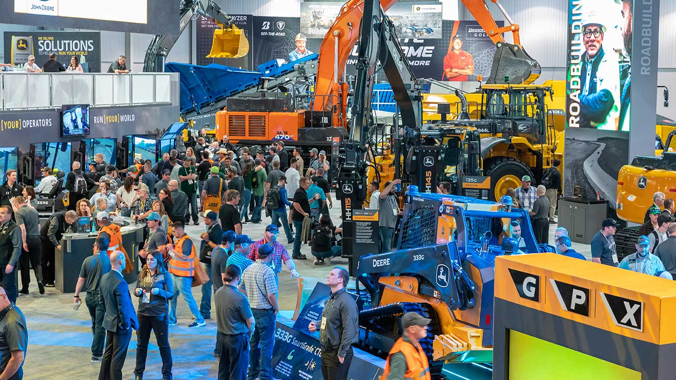 A high-level view of the John Deere booth showing a Hitachi excavator in the background