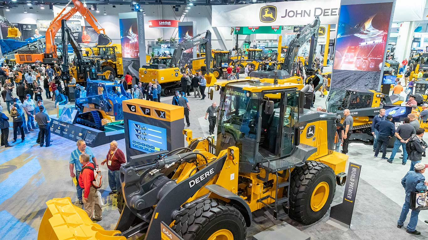 Wide view of the John Deere booth with the 644 G-Tier loader in the foreground