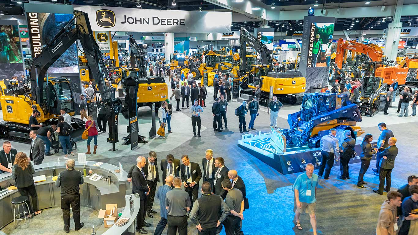 A high-level view of the John Deere booth showing dozens of machines and a large crowd